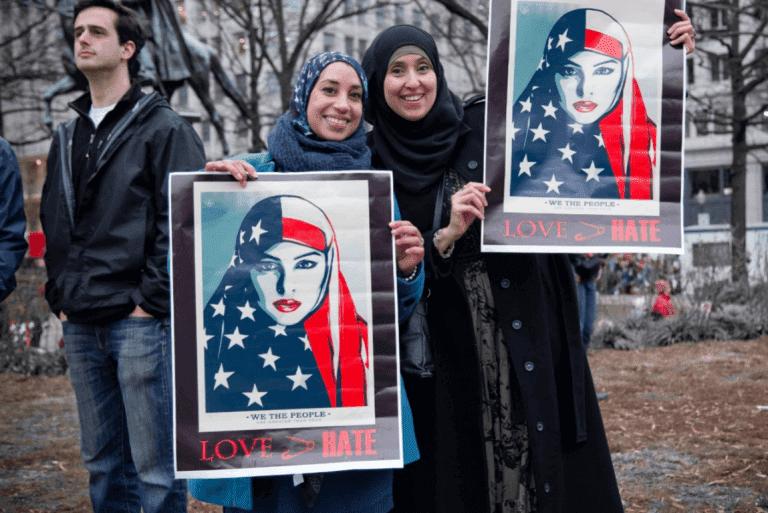 Zwei muslimische Frauen halten stolz Plakate gegen Fremdenfeindlichkeit hoch.