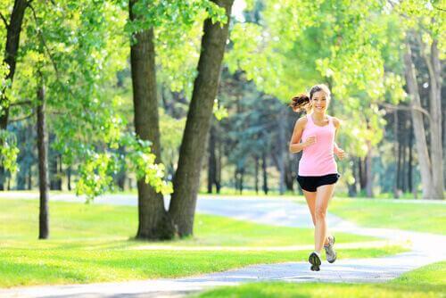 Eine junge Frau joggt durch den Park.