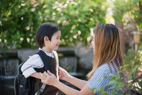 Junge mit Rucksack spricht mit seiner Mutter über die Schule