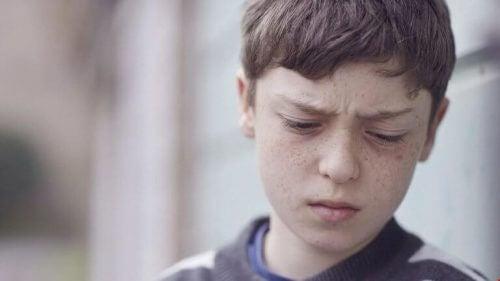 Junge mit Kindheitstrauma schaut betroffen nach unten