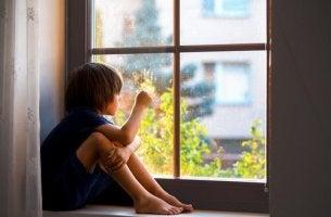 Trennungsangst - Junge schaut traurig aus dem Fenster