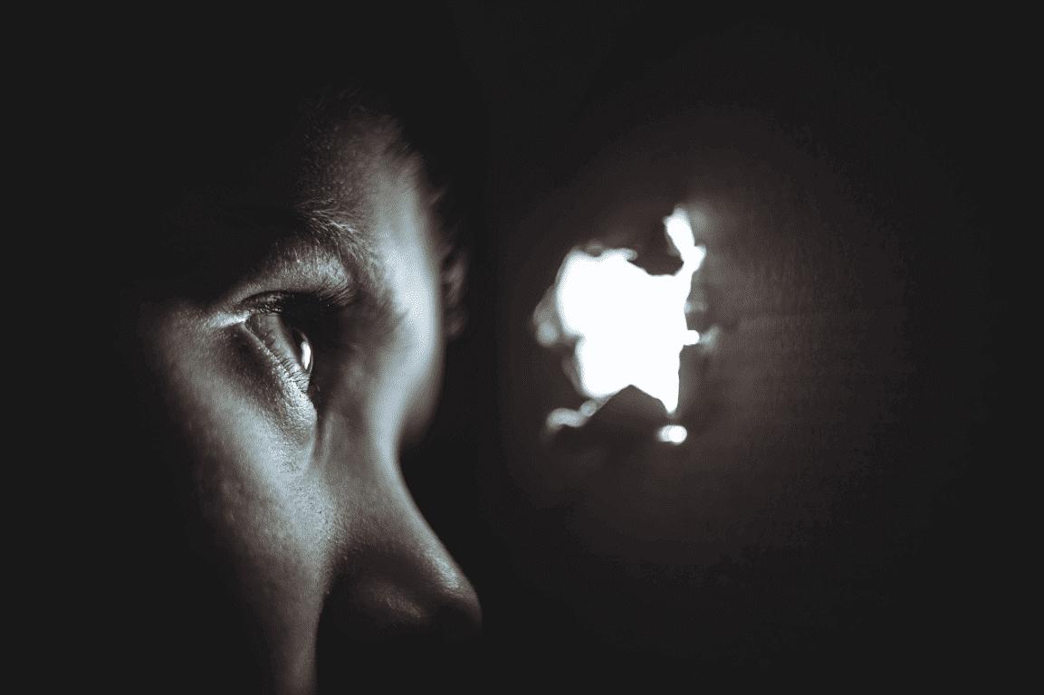 Junge schaut aus einem Loch in einer Box hinaus.
