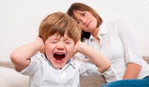 Junge schreit und hält sich die Ohren zu