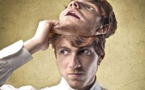 Junger Mann streift seine Maske ab
