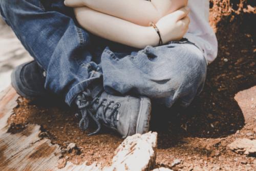 Ein Kind hat seine Arme um sich geschlungen.