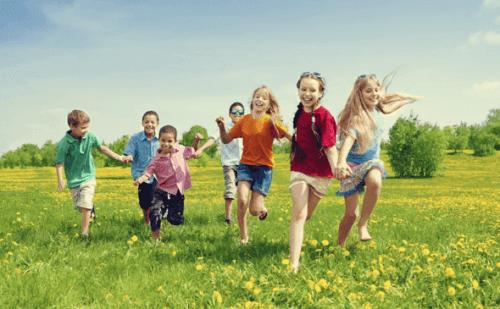 Eine Gruppe Kinder rennt über eine grüne Wiese.