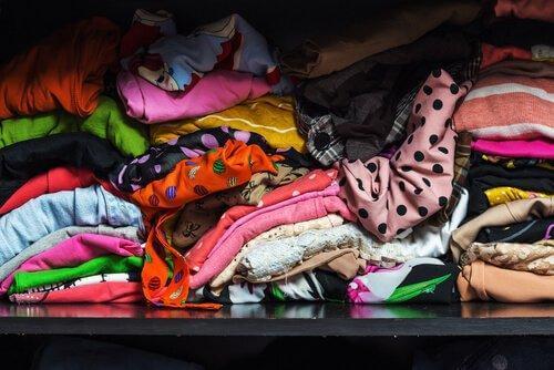 Verschiedene Kleidung ist chaotisch übereinander geworfen, was ein Anzeichen für das Messie-Syndrom ist.