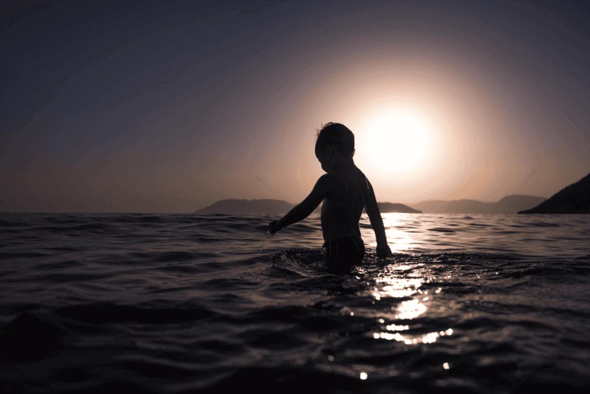 Kleiner Junge badet im Meer