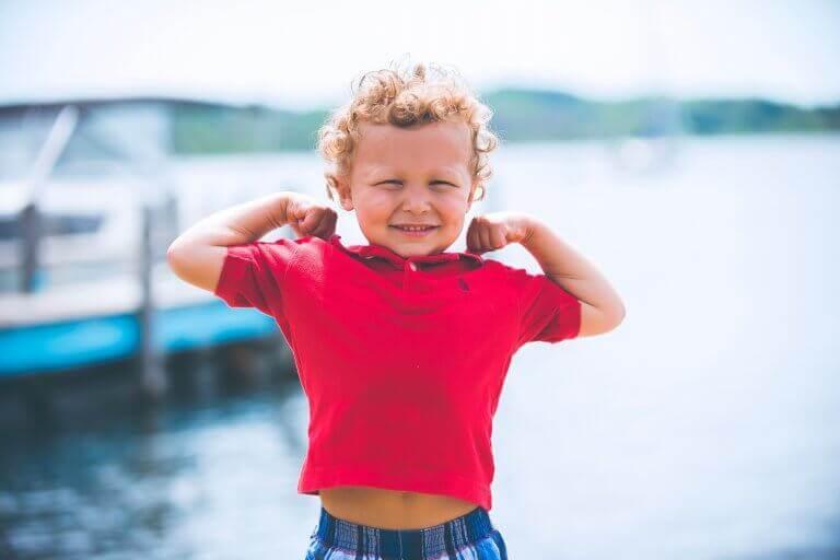 Kleiner Junge zeigt stolz seinen Bizeps