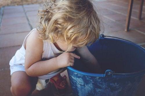 Ein kleines Mädchen greift in einen Eimer