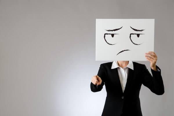 Frau hält sich Papier mit traurigem Gesicht vor den Kopf