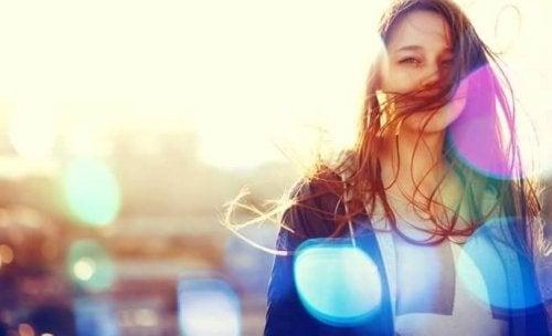 Lächelnde Frau mit Sonnenstrahlen im Hintergrund