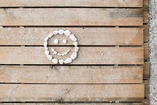 Lächelndes Gesicht aus Steinen auf Holzunterlage