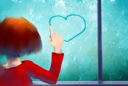 Mädchen malt Herz an vereiste Scheibe.