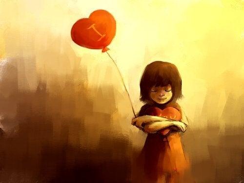 Mädchen hält Herzluftballon an einer Schnur.