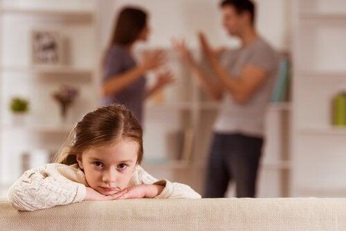 Mädchen an einem Tisch; im Hintergrund streiten die Eltern