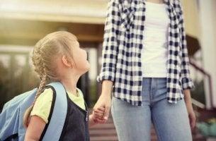 Erster Schultag - Mädchen hält die Hand ihrer Mutter