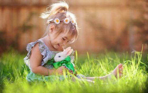 Ein Mädchen sitzt auf einer Wiese und hält einen Stoffhasen.