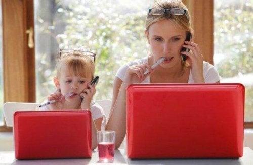 Ein Mädchen starrt in einen Laptop, mit einer Brille auf dem Kopf, Stift im Mund und Handy am Ohr und imitiert damit exakt die Frau neben ihr.