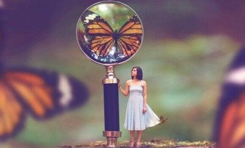 Mädchen mit Lupe, die auf einen Schmetterling zeigt