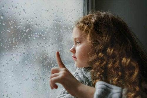 Mädchen schaut aus einem verregneten Fenster