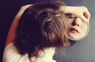 Traurigkeit verstecken - Mädchen schaut in einen Spiegel