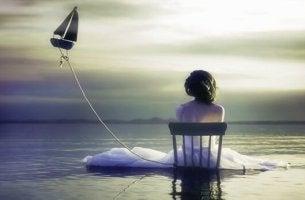 Mädchen sitzt auf einem Stuhl im Meer