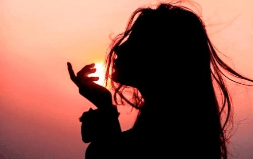 Mädchen steht vor Sonnenuntergang.