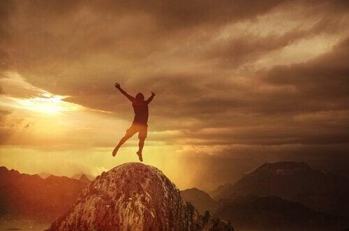 Ein Mann auf einem Berggipfel, während die Sonne untergeht. Er reckt seine Arme zum Himmel.
