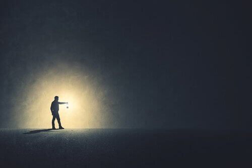 Ein Mann hält ein Licht in der Dunkelheit.