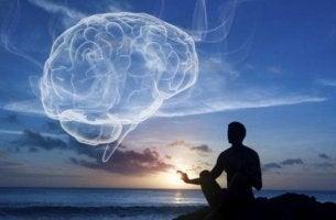 Wellness - Mann meditiert und am Himmel eine Wolke in Form eines Gehirns