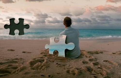 Ein Mann, angelehnt an ein Puzzelteil, sitzt am Strand und blickt auf das Meer.