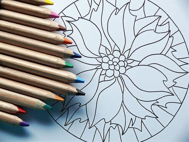 Mandala, auf dem Buntstifte liegen