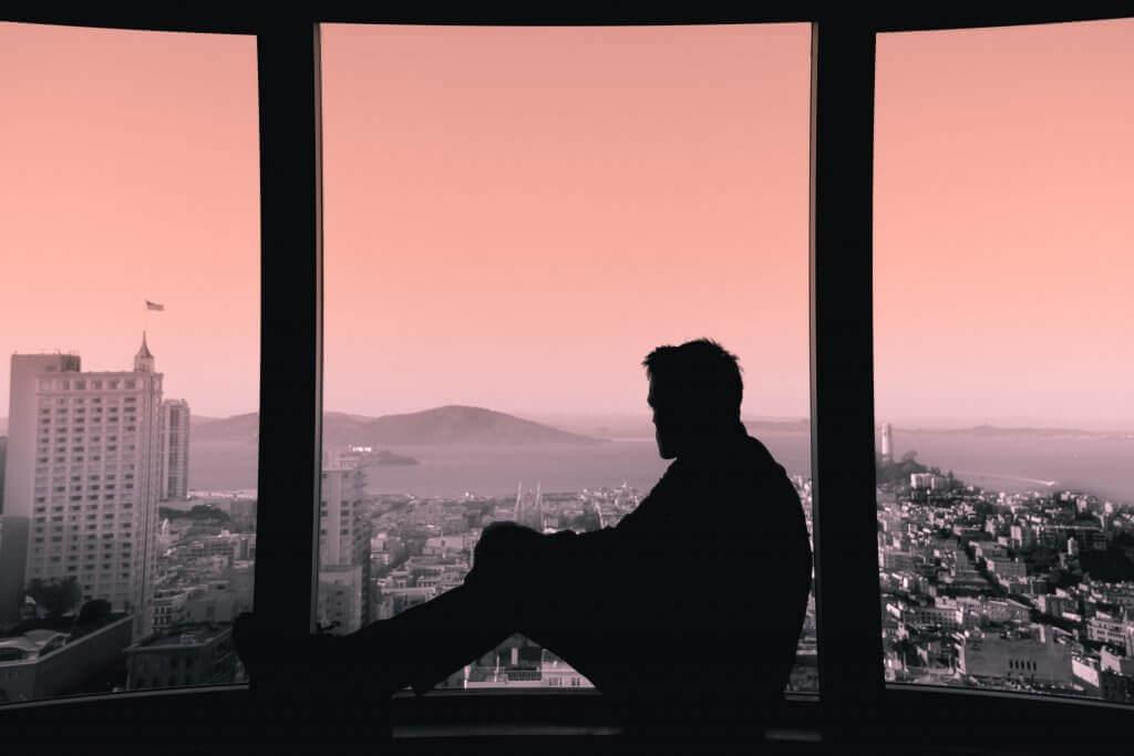 Mann sitzt allein an einem Fenster