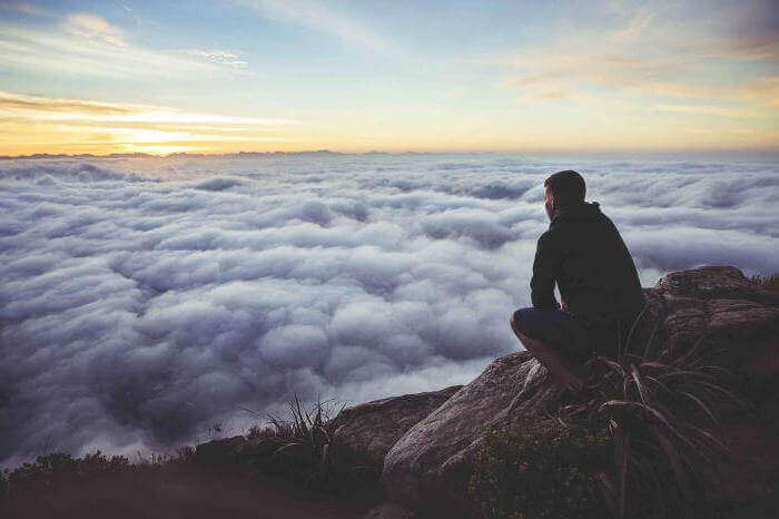Mann sitzt auf einem Berg und schaut auf eine Wolkendecke