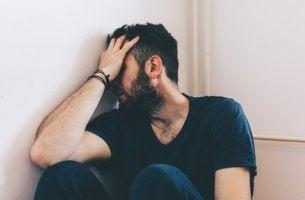 Ein Mann lehnt an der Wand und verdeckt sein Gesicht.