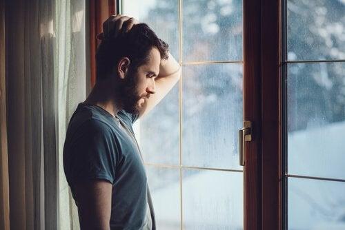 Mann mit Hand auf dem Kopf steht vor einem Fenster in Winterlandschaft