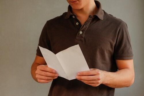 Ein junger Mann hält einen gefalteten Zettel in seinen Händen.