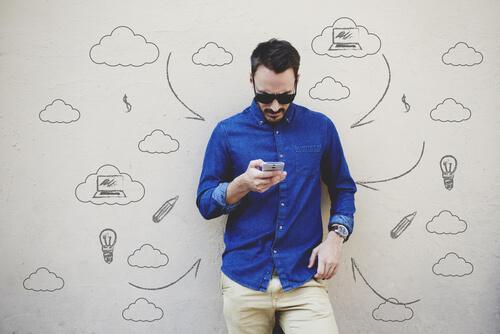 Neue Arten der Kommunikation: Ein Mann starrt auf sein Handy; auf der weißen Wand hinter ihm sind kleine Zeichnungen dargestellt, unter anderem Gedankenblasen oder eine Glühbirne.