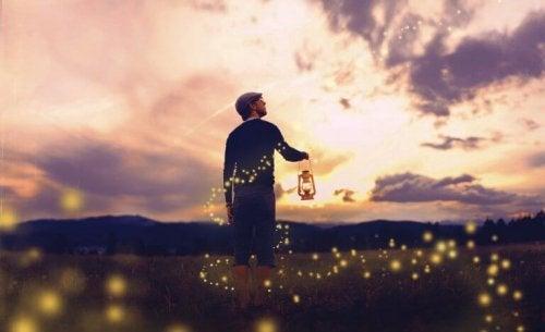 Mann mit Lampe auf einem Feld, ein Symbol, das ausdrückt: Das Leben ist schön.
