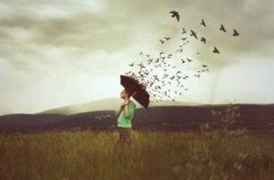 Dich dem stellen, was dich verletzt - Mann mit Schirm, über dem zahlreiche Vögel fliegen