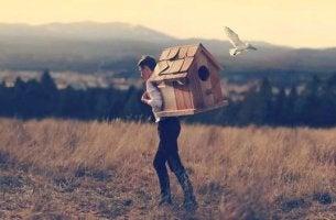 Ermutigung für schwere Zeiten - Ein Mann trägt ein großes Vogelhaus am Rücken und spaziert damit durch ein Feld.