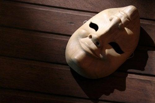 Eine Maske, die ein lächelndes und trauriges Gesicht zeigt, liegt auf dem Boden.