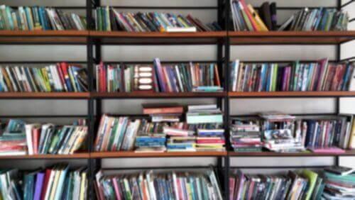 Ein ungeordnetes Bücherregal, das mit Büchern vollgestopft ist