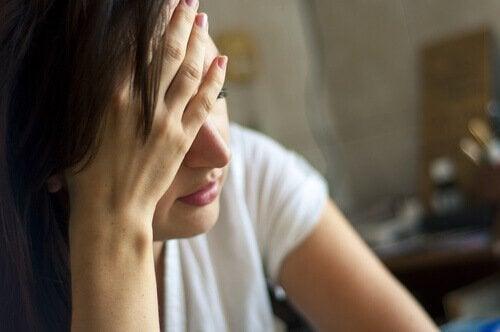 Frau stützt erschöpft ihren Kopf ab.