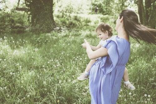 Mutter und Kind tanzen im Garten