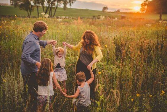 Eine Familie spielt und tanz auf einer grünen Wiese