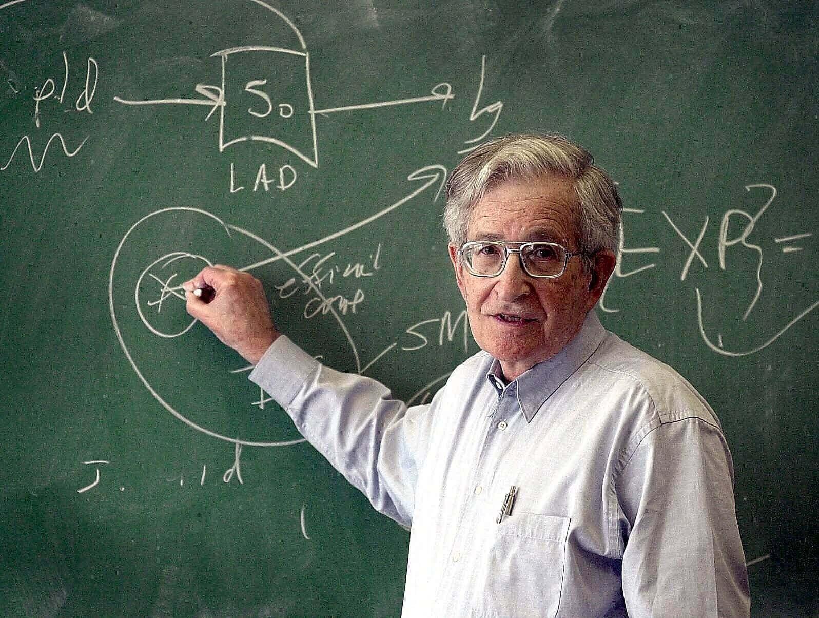 Noam Chomsky schreibt auf einer Tafel
