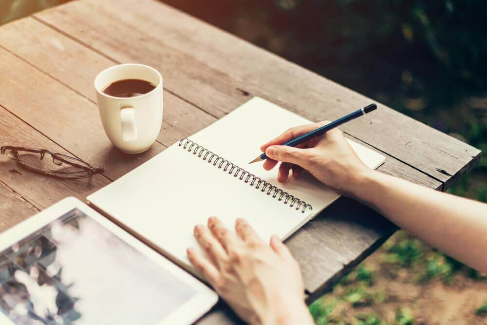 Notizblock liegt neben einer Tasse Kaffee