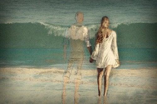 Ein Paar geht Hand in Hand am Strand spazieren; der Mann ist nur transparent zu sehen.